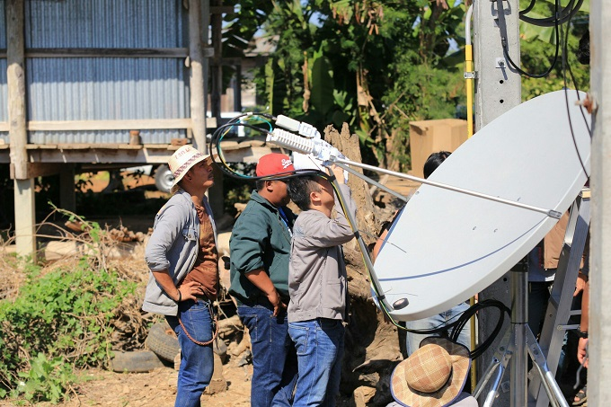 Engineers installing a satellite antenna in Thailand 680 width